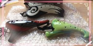 [Image Description: a photo of my three ocarinas: Sumi (black & white), Aria (black & red), Air (Green) from STL Ocarina].